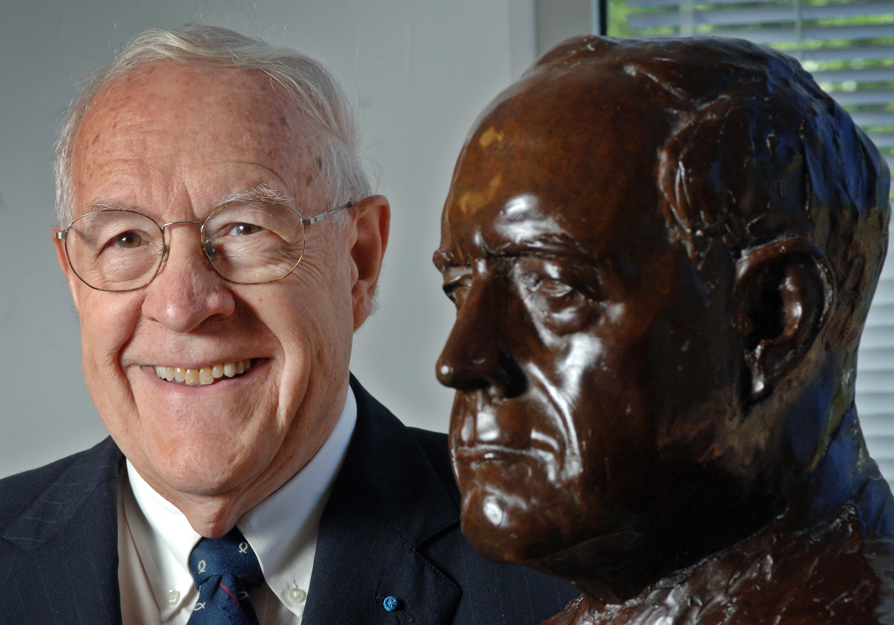 Fred Brooks poses with a bust made in his honor in Sitterson Hall. (photo by Dan Sears)