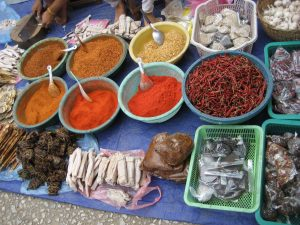 An outdoor market in Laos features spices and water buffalo jerky (white strips, bottom center), which is added to a spicy dipping sauce. (photo by Katy Clune)