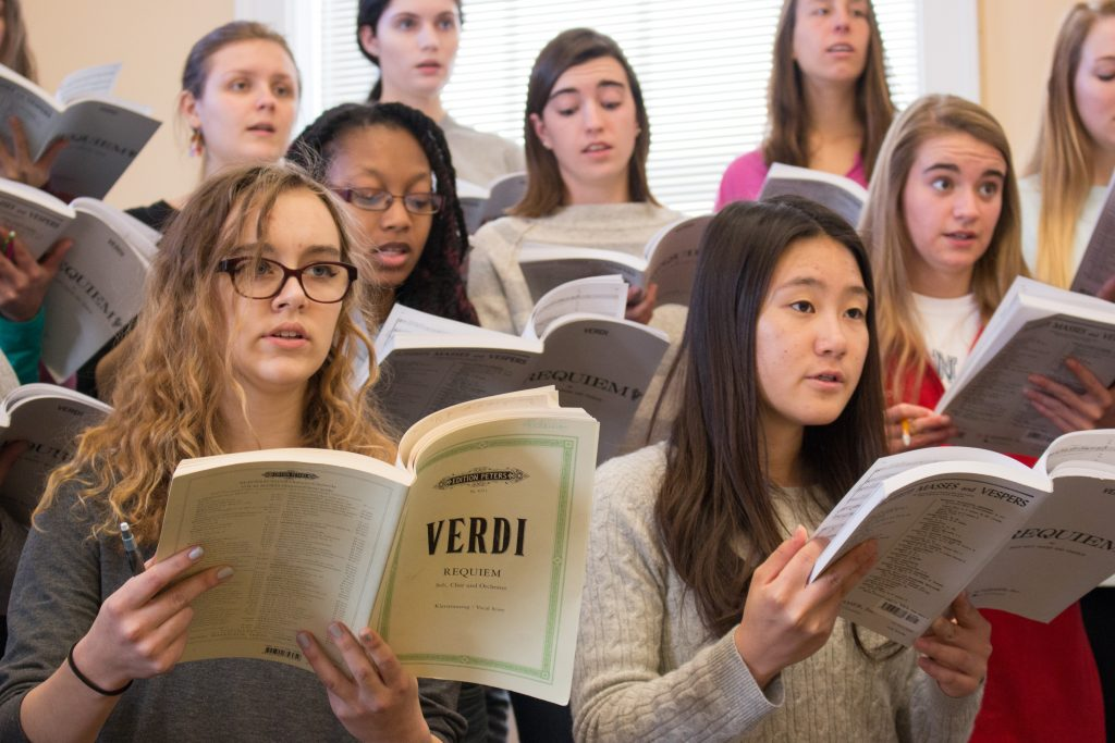 Members of the Carolina Choir, one of four choral groups performing the Defiant Requiem, practice at a rehearsal led by Susan Klebanow. (photo by Kristen Chavez)