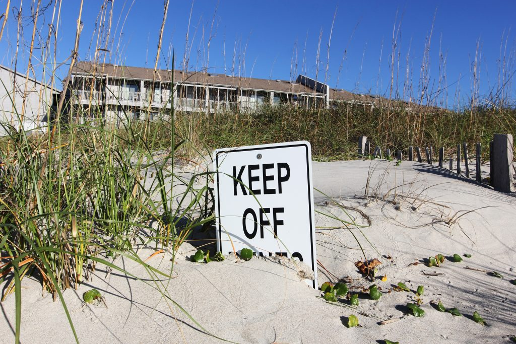 An old wooden sign at Atlantic Beach warns people to keep off the dunes to protect the fragile ecosystem. (photo by Mary Lide Parker)