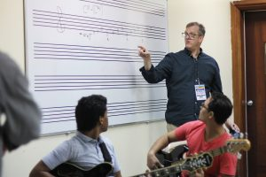 Steve Anderson stands at a whiteboard and explains some of the theory behind improvisation in jazz composition at the National Conservatory of Music in Santo Domingo.