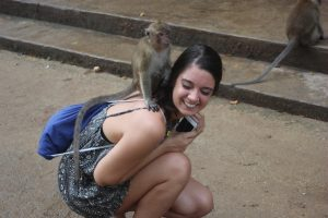 Amanda Davis makes a new friend, a monkey, at a cave temple in Thailand.