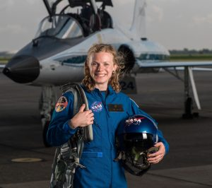 Carolina alumna Zena Cardman stands on a tarmac holding her gear. She is a new NASA astronaut trainee. Over 18,000 people applied to be in the 2017 class; she was one of 12 selected.
