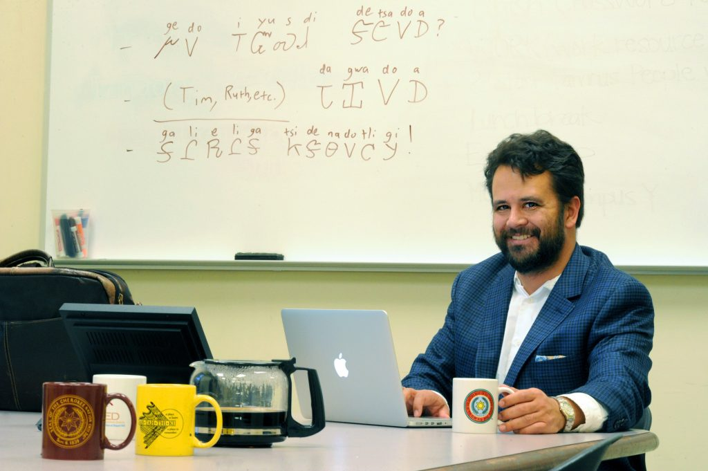 American studies assistant professor Ben Frey at his computer with a coffee pot and surrounding mugs. Words in Cherokee is written on the board behind him.