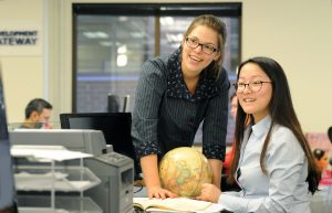 Ying He, seated, confers with co-worker Meg VanDeusen at Feedback Labs.