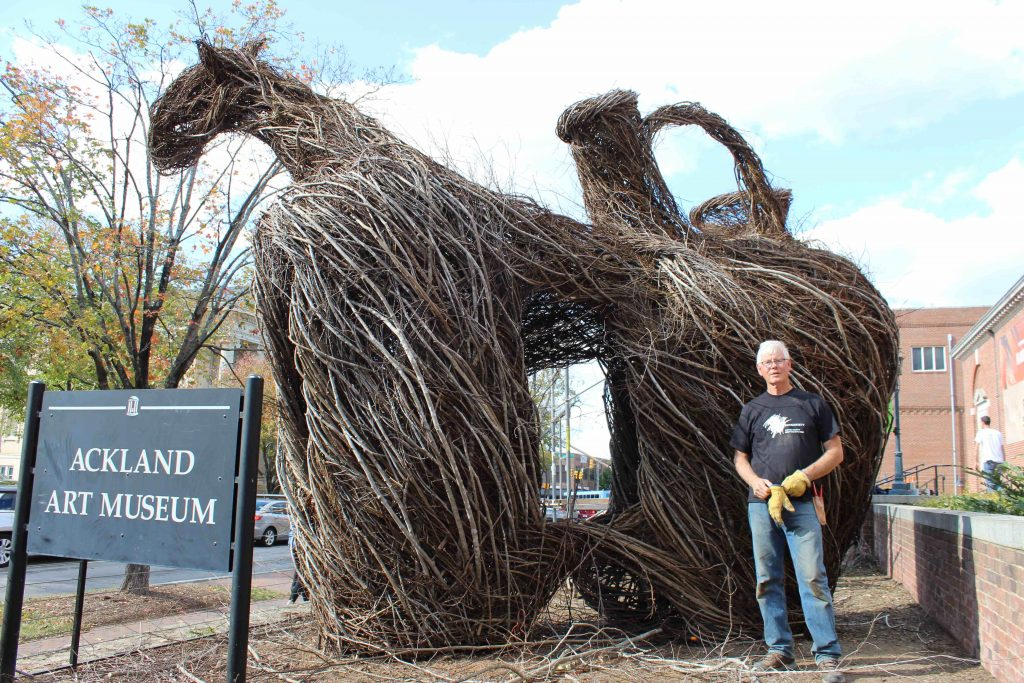 Patrick Dougherty poses in front of one of the stickwork sculptures outside of Ackland Art Museum.