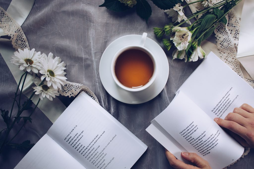 photo of open books with a cup of coffee on a table and flowers surrounding the books and coffee