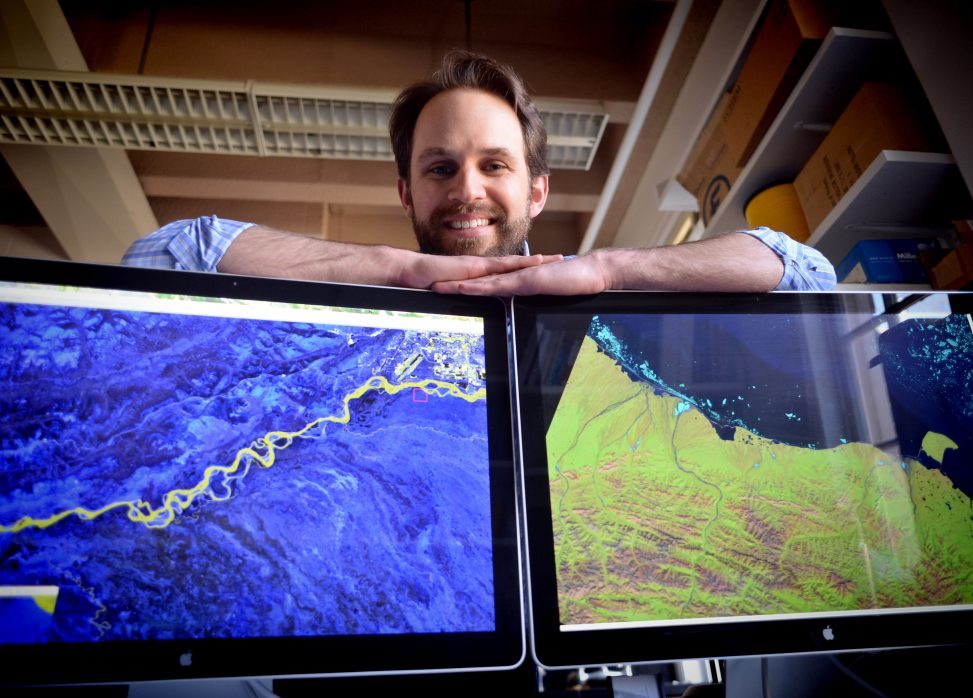 Tamlin Pavelsky with Landsat images of the Alaska coast and the Tanana River in his office in Mitchell Hall at the University of North Carolina at Chapel Hill. (photo by Dan Sears)