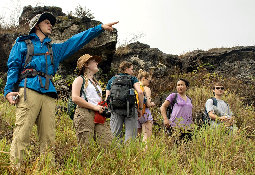 On one of the Galapagos Islands, a student points while other students look on.