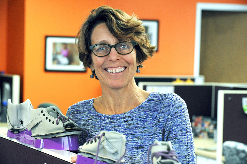 Photo of a smiling Chesca Colloredo-Mansfeld in her office with a model of the clubfoot treatment brace by Donn Young.