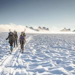 Researchers ski across the Juneau Icefield, carrying shovels