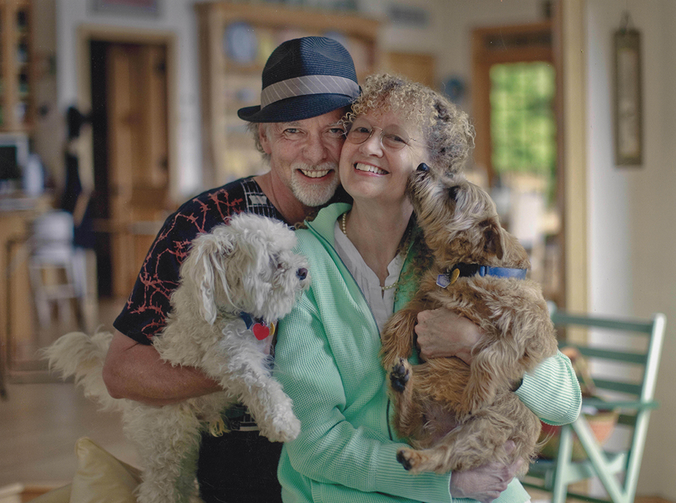 Together Mary Pope Osborne and Will Osborne oversee the Magic Tree House enterprise. They are pictured smiling and facing the camera and holding two of their dogs in their arms.(photo by Wendy Carlson)