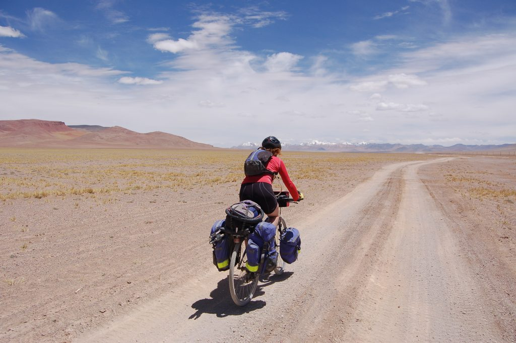Photo of biker Mel Yule biking the Silk Road with her bicycle loaded down with gear. (Photo by Kate Harris)