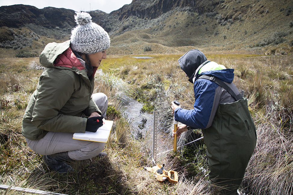 Two researchers, bundled in winter clothes, track measurements of a stream in a scenic environment