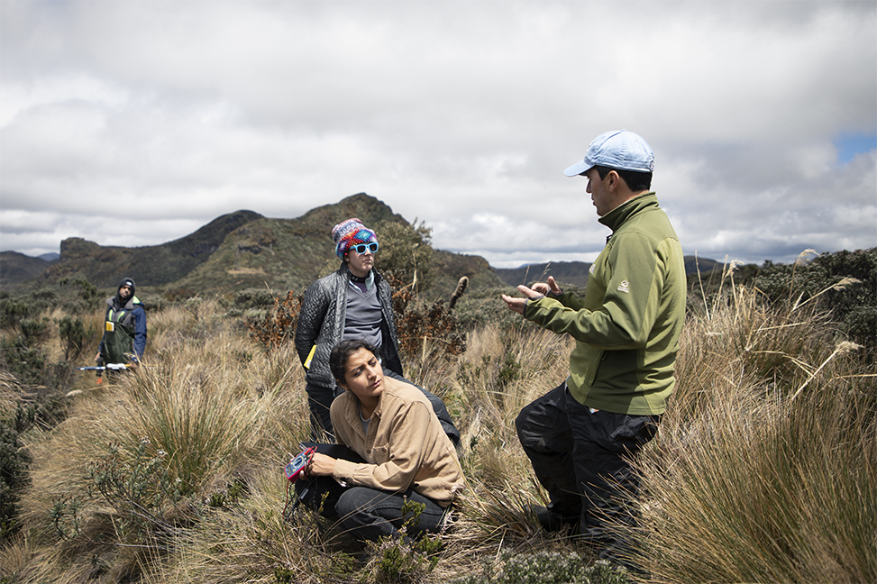 Diego Riveros-Iregui stands and talks to students at a stream site.