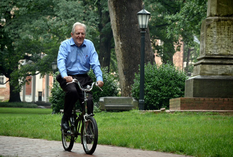 Christopher Armitage passes by the Davie Poplar and the Caldwell Monument on McCorkle Place on his bicycle