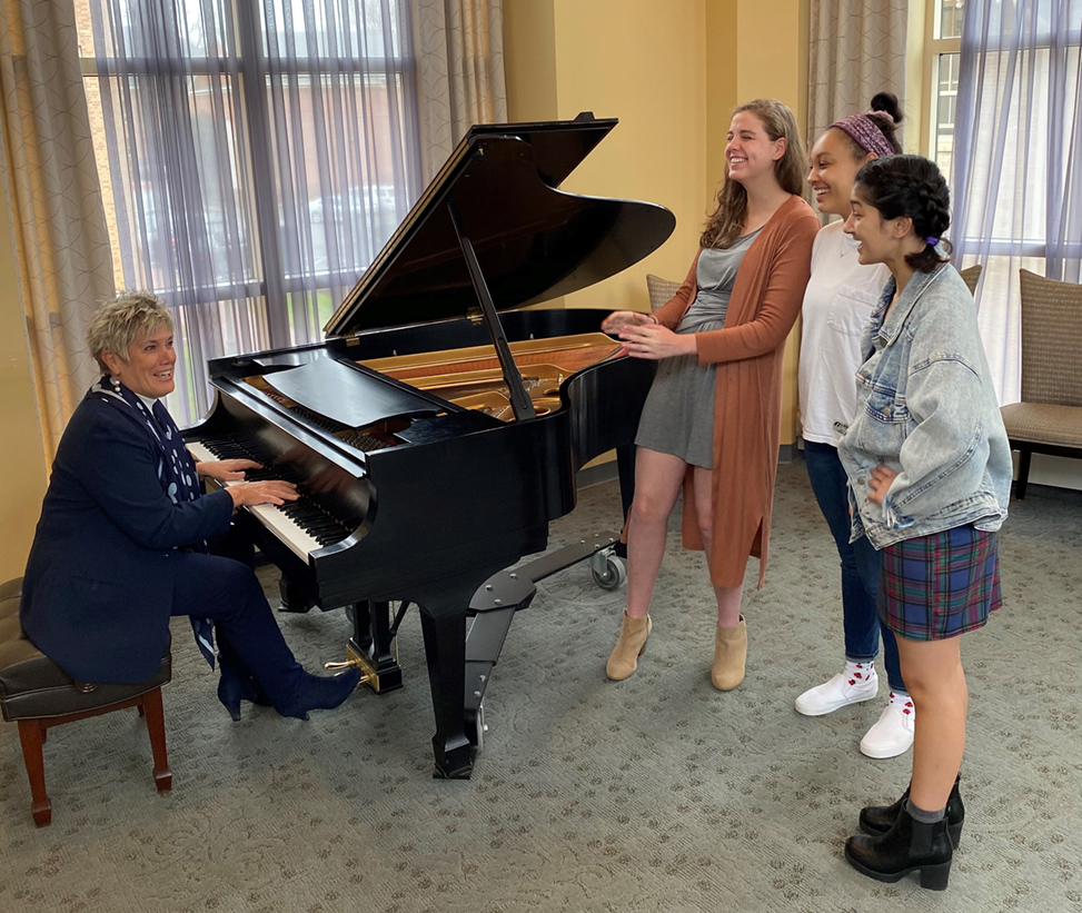Terry Rhodes, at the piano, plays music with three students