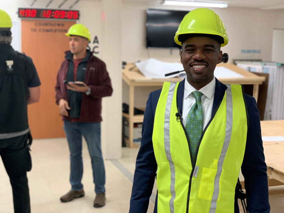 Elijah Heyward wears a yellow vest and hard hat at the construction site for the new International African American Museum in Charleston.