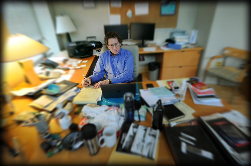 Adam Versényi works in his office, with a blurred effect around him.