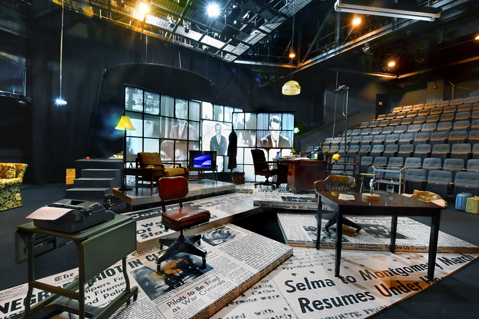 The Edges of Time set in the Paul Green Theatre. The floor is decorated with large images of historic newspapers, including those from the Civil Rights Movement. Three desks are set up in different corners, as well as a chair near a small television. The back display has multiple screens, which show historic clips of various news anchors.