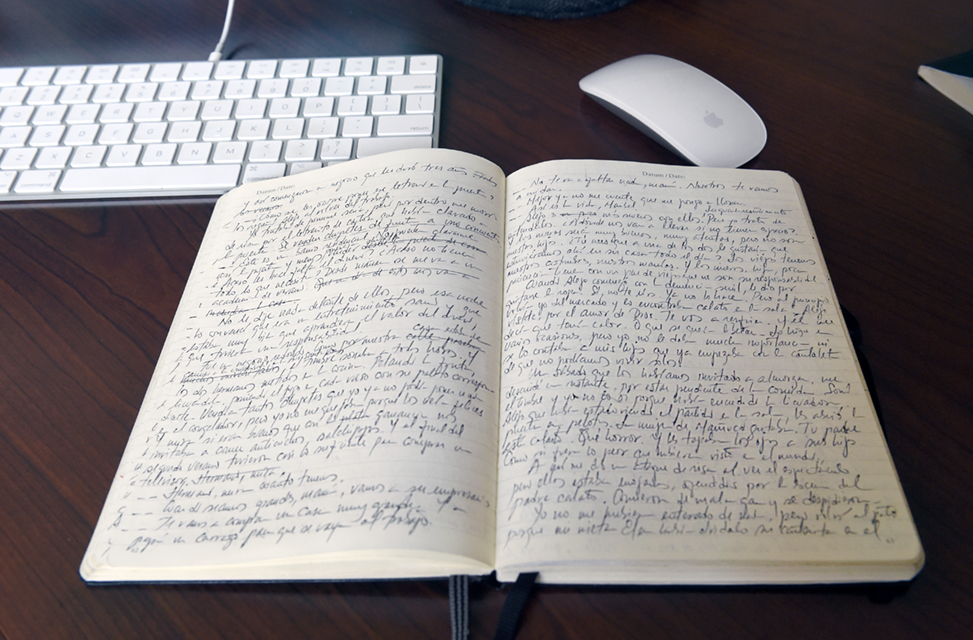Notes written across two pages from Oswaldo Estrada's journal, on his desk next to a computer laptop and mouse.