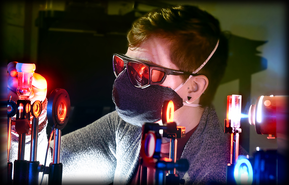 Rachel Bangle works in the laser lab with a mask on and pulsing lights around her.