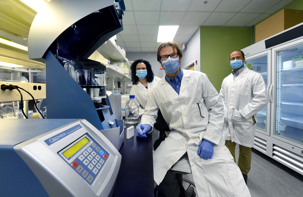 Samantha Pattenden, Paul Dayton and Sunny Kasoji wear lab coats and masks in the Triangle Biotechnology lab in Research Triangle Park.