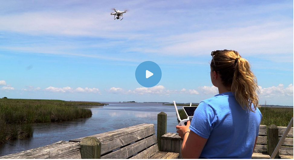 Photo of a female researcher flying a drone with her back to the camera.