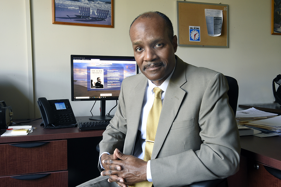 Claude Clegg, dressed in a suit, sits at his desk and smiles at the camera with a computer screen in the background with a picture of his Obama book cover.