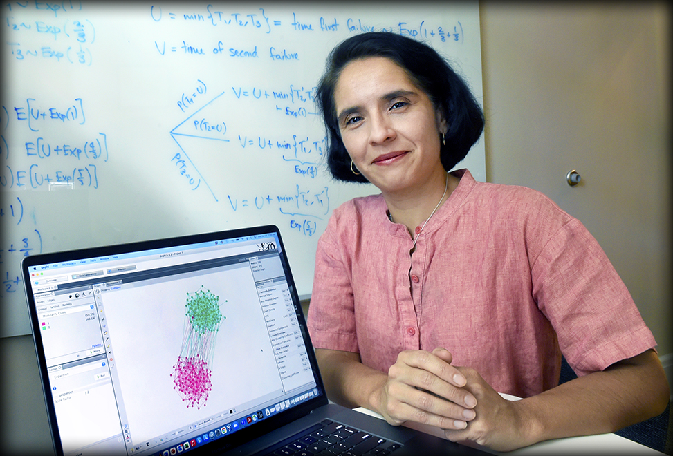 Mariana Olvera pictured smiling beside her computer showing a mathematical model. She is sitting in front of a whiteboard filled with formulas.